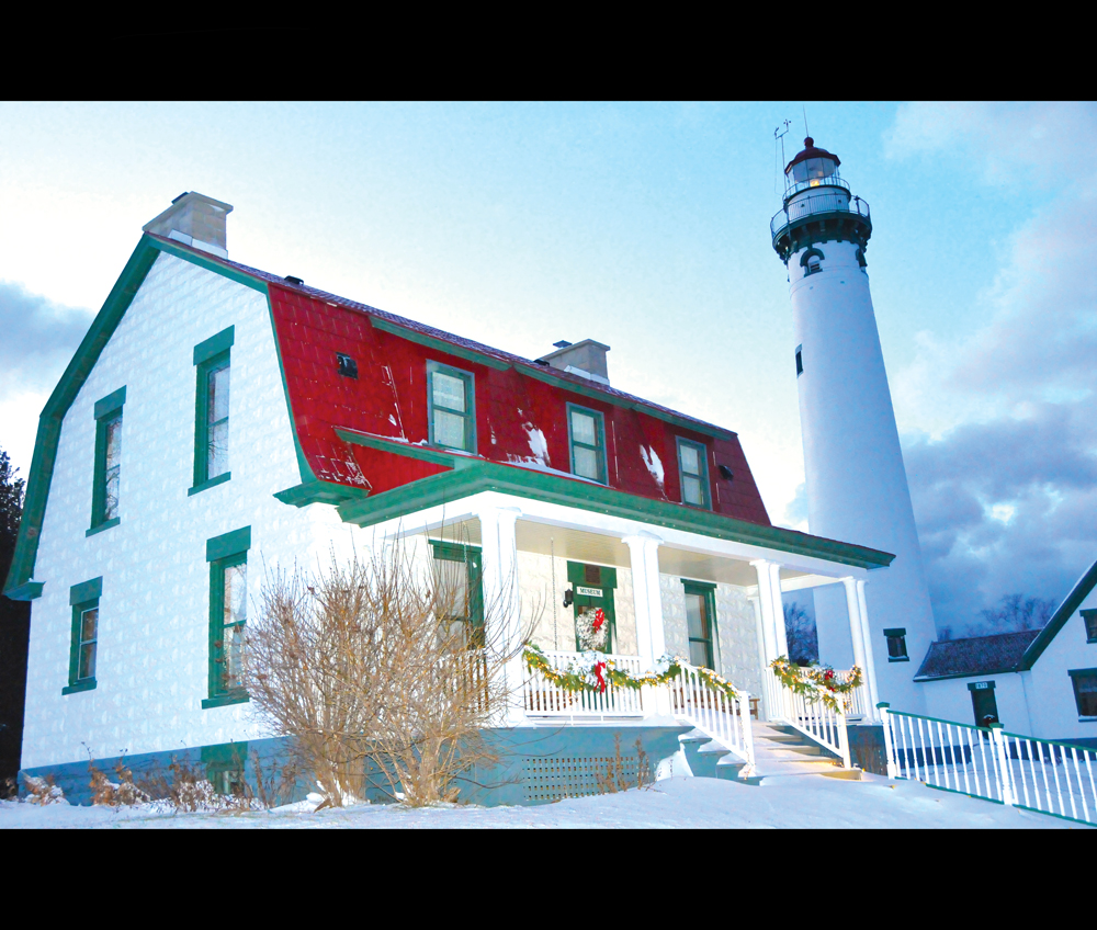 THE FRONT steps of the 1905 keeper's house on the lighthouse peninsula will need a little shoveling for Friday's carolers. The rest of the snow can stay right where it is because the setting at New Presque Isle Lighthouse Park is one to behold this time of year. (Photo by Peter Jakey)